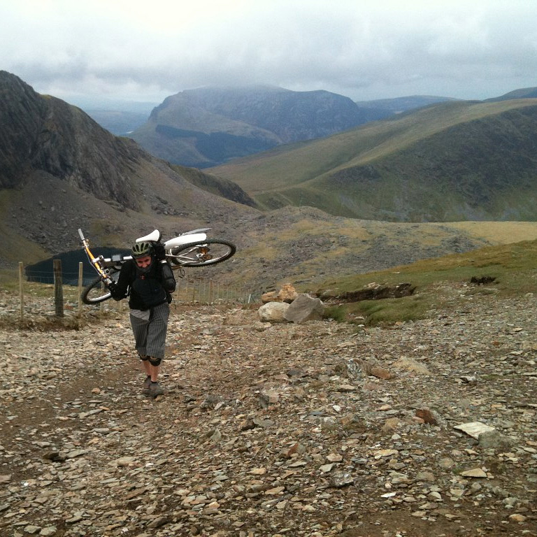 Andy carries his bike on Snowdon